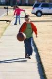 Le garçon a plaisir à rebondir le basket-ball en bas de la rue photos stock