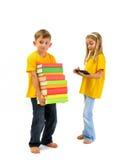 Le garçon portant les livres lourds, fille a un eBook Photographie stock libre de droits