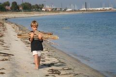 Le garçon porte le bois de chauffage images libres de droits