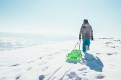 Le garçon porte le traîneau sur la colline neigeuse et apprécier le winte photos libres de droits