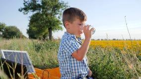 Le garçon près du chargeur solaire se tient en verre de mains à l'air ouvert, à l'enfant s'asseyant près de la batterie solaire a banque de vidéos