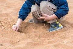 Le garçon préscolaire d'âge s'assied dans le sable et creuse un trou avec ses mains Image stock