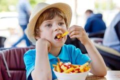 Le garçon préscolaire en bonne santé mignon d'enfant mange des pommes frites avec le ketchup photos stock
