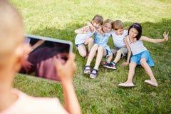 Le garçon prend la photographie des enfants avec le comprimé Photographie stock