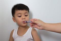 Le garçon prend le médicament de la seringue photographie stock
