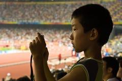 Le garçon prend une photo aux Jeux Olympiques Photographie stock libre de droits
