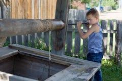 Le garçon prend une position avec de l'eau photos stock