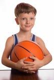 Le garçon pressant une boule de basket-ball à un sein Image stock