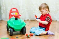 Le garçon répare l'automobile photographie stock