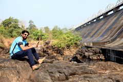 Le garçon regardant un barrage s'asseyent près d'une rivière dans l'Inde de maharashtra photographie stock libre de droits