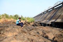 Le garçon regardant un barrage s'asseyent près d'une rivière dans l'Inde de maharashtra images libres de droits