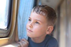 Le garçon regarde dans l'hublot du `s de train Image libre de droits