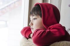 Le garçon regarde dehors. photographie stock
