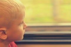 Le garçon regarde la fenêtre de la voiture de train Photo libre de droits