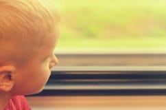 Le garçon regarde la fenêtre de la voiture de train Photos stock