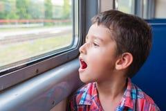 Le garçon regarde la fenêtre du train Photographie stock libre de droits
