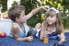Le garçon regarde les petites fleurs dans les cheveux de filles Image stock