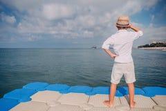 Le garçon regarde sur le bateau sur l'horizon de la jetée de mer Photographie stock
