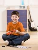Le garçon remontant pièce du petit véhicule modèle Image stock