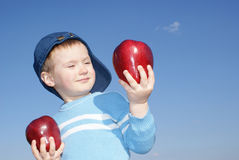 Le garçon retient de grandes pommes rouges Photographie stock libre de droits