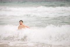 Le garçon riant heureux saute par-dessus les marées de mer Photographie stock libre de droits