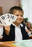 Le garçon ridicule affiche des cartes avec des figures Image stock