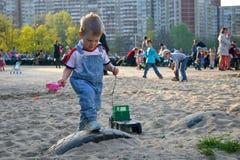 Le garçon roule la voiture de jouet sur le terrain de jeu Photo stock