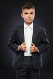 Le garçon sérieux ajuste son costume noir Photographie stock libre de droits