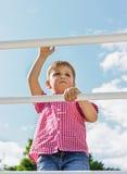 Le garçon s'élève sur une échelle, une vue inférieure, en plein air agains Photos stock
