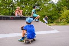 Le garçon s'asseyant observant ses amis au patin se garent Photo stock