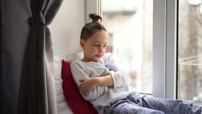 Le garçon s'asseyant sur le filon-couche de fenêtre et mesurent la température banque de vidéos