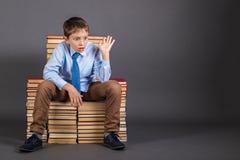 Le garçon s'asseyant sur le trône des livres Images stock