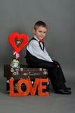 Le garçon s'asseyant sur une valise avec les mots aiment Photo libre de droits
