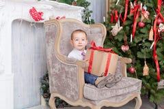 Le garçon s'asseyent dans une chaise avec des cadeaux Photo stock