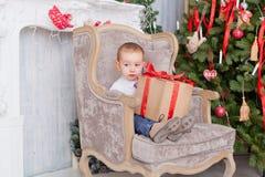 Le garçon s'asseyent dans une chaise avec des cadeaux Photographie stock