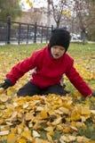le garçon s'asseyent sur des feuilles Photos stock