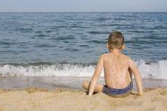 Le garçon s'assied à l'eau Photo stock