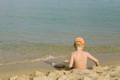 Le garçon s'assied à l'eau Image libre de droits