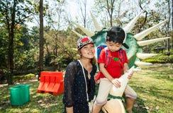 Le garçon s'assied autour de la statue de dinosaure Photos stock