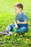 Le garçon s'assied dans l'herbe Photographie stock libre de droits