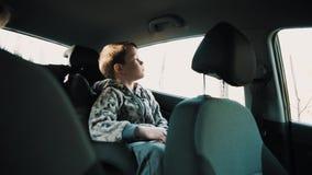 Le garçon s'assied dans la chaise et la vague de voiture d'enfant au revoir au papa banque de vidéos