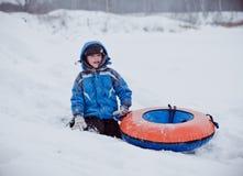 Le garçon s'assied dans la neige, tenant la tuyauterie Images libres de droits