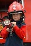 Le garçon s'assied dans un camion de pompiers Photo libre de droits