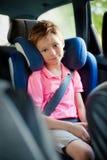 le garçon s'assied dans un siège de voiture Images stock