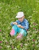 Le garçon s'assied dans une herbe Photographie stock