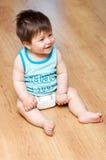 Le garçon s'assied sur l'étage de bois dur Photographie stock libre de droits