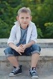 Le garçon s'assied sur l'attente de roches Images stock