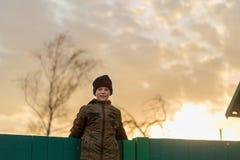 Le garçon s'assied sur la barrière au coucher du soleil Image libre de droits