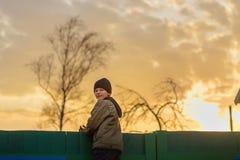 Le garçon s'assied sur la barrière au coucher du soleil Images stock