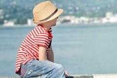 Le garçon s'assied sur la plage avec un chapeau et le T-shirt rayé, examine la distance Vue de côté Images libres de droits